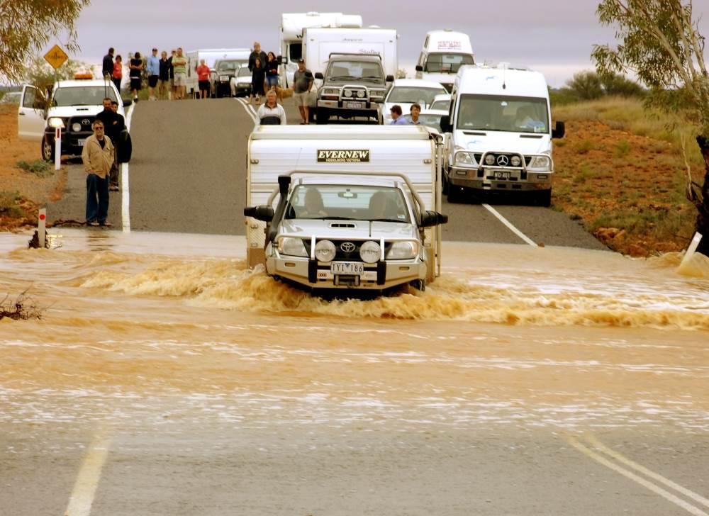 ute towing caravan crosses flooded stream